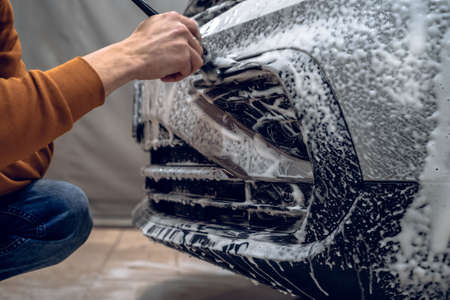 Car wash detailing. Worker cleans bumper with auto shampoo foam and brush, detailed vehicle cleaning, close up.