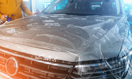 Paint Protection Film or PPF polymer protection coating layer, installing and wrapping on car hood in Detailing Garage.