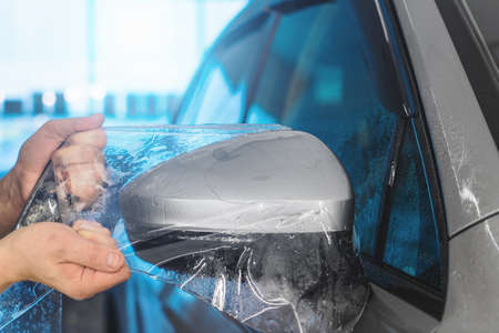 PPF installation on car side mirror. Paint Protection Film is protective polyurethane coating for paintwork on car. Reklamní fotografie