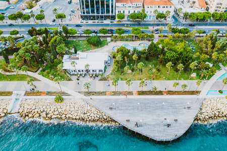 Molos Promenade park with alley and wooden pier for walking people, aerial view. Limassol city coastline,Cyprus.