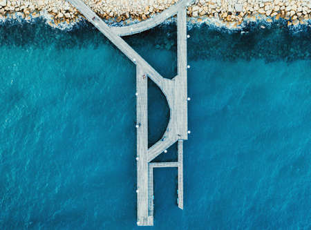 Aerial top view of wooden pier at Limassol Molos Park and blue sea surface.