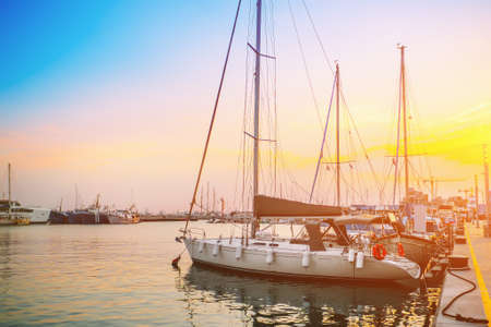 Boats and yachts in sea marina in old Limassol port at sunset, harbor in mediterranean coast, Limassol, Cyprus.