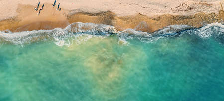 Empty tropical sand beach and azure sea or ocean water aerial top view from drone, panoramic long banner with copy space.