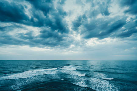 Dark blue clouds and sea or ocean water surface with foam waves before storm, dramatic seascape. Reklamní fotografie