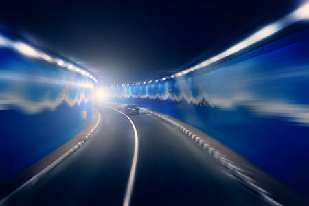 Road tunnel with riding car in blurred motion effect. Imagens