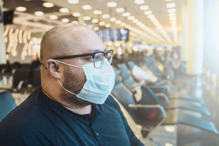 Man in glasses in protective face mask waiting to board at terminal airport chair. Airplane transportation by work or travel