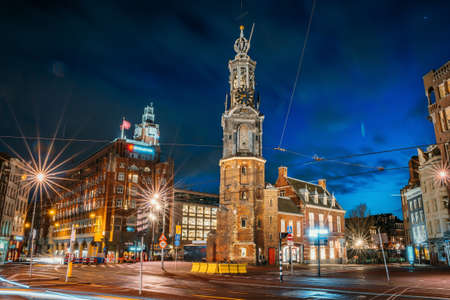 Munttoren or Mint Tower or Munt in Amsterdam historical center at night, Netherlands.