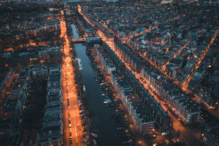 Amsterdam, Netherlands. Aerial top view of old city from above at night with canals and houses.
