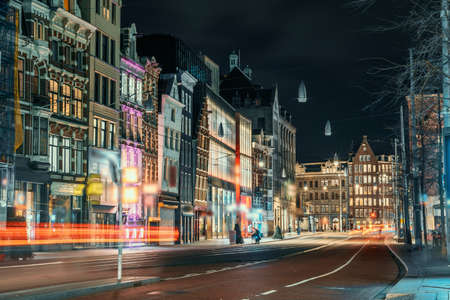 Night city view of Amsterdam city, street with illuminated buildings of old European city, Netherlands.