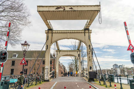 Amsterdam, Netherlands - March 2020: Magere Brug or Skinny Bridge on Amstel river, bascule bridge made of white-painted wood.