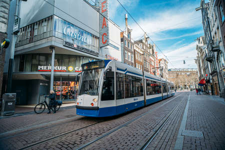 Amsterdam, Netherlands - March 2020: Tram in downtown of Amsterdam, street scene from historical center with public rail transportation, people and old architecture with shops or stores. Editorial