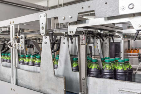 Plastic bottles with juice in beverage factory modern automated conveyor line or belt. Imagens