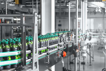 Industrial beverage factory interior with automated computerized conveyor line or belt and plastic bottles with organic juice.