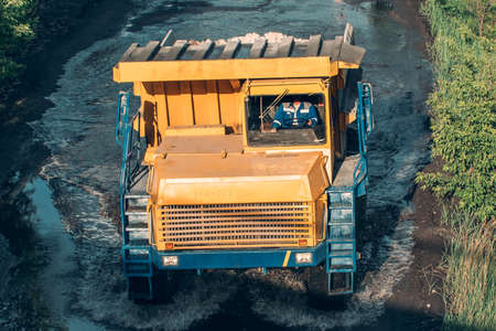 Big yellow mining truck in open pit mine industry.