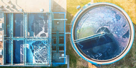 Outdoor water plant cleaning facility. Water purification in round sedimentation tank, aerial top view. Imagens