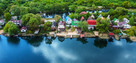 Small suburban houses on river bank with blue sky reflection in water and green trees forest on background, aerial view from drone.