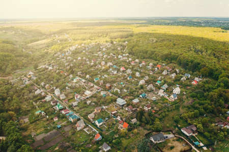 Suburban small village with houses in green nature forest with fresh air, aerial view from drone.