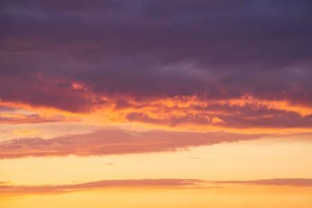 Bright violet or purple clouds at epic orange sunset sky background. 免版税图像