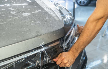 Car protection film or PPF process of wrapping and installing on car hood by detailer worker hands, close up. Imagens