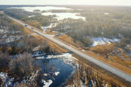 Aerial view of asphalt road in sunshine between frozen rivers and lakes with rural forest in Karelia, adventure and tourism concept. Imagens
