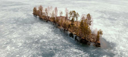 Aerial top view small island in middle of ice-frozen river or lake in Karelia.