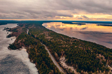 Aerial view of Karelia nature landscape with rivers and island with pine trees in spring evening.