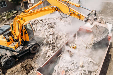 Excavator loads construction waste into truck for removal from construction site. Demolition of dilapidated housing for new development, aerial view