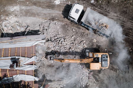 Demolition of building by industrial excavator. Bucket breaks walls and roof of old house full of dust, aerial view. Foto de archivo