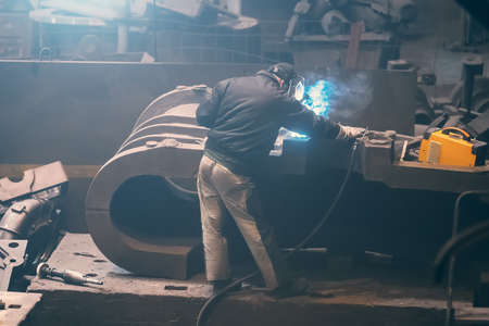 Welder processes large cast iron part in metallurgical plant after it has been melted or manufactured.