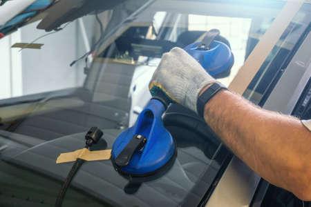 Mechanic changes windscreen or windshield on car close up. Foto de archivo