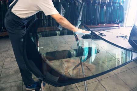 Automobile glazier worker degreases glass windscreen or windshield before installation on car in service station garage.