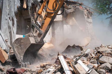 Hydraulic excavator bucket breaks down old building. Wreckage and industrial debris in dust, house demolition.