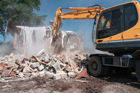 House demolition. Big yellow excavator breaks building for new construction.