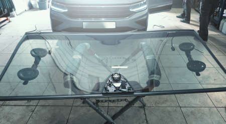 Glass windscreen or windshield before installation on car in service station garage.