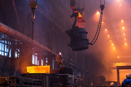 Big ladle on crane before melting in foundry workshop. Smelting of multi-ton cast iron parts. Metallurgical plant or Steel Mill.