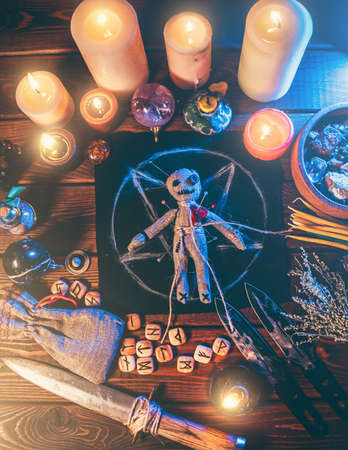 Voodoo doll studded with needles in center of magical table with candles and occult objects top view. Magic and dark spooky ritual. Retribution or revenge through witchcraft concept.