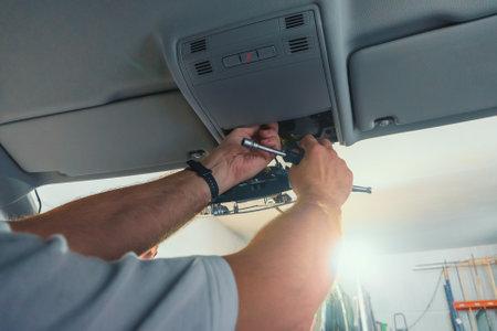 Car repair. Serviceman repairs electrical wiring inside car. Replacing windshield with disconnecting sensors.