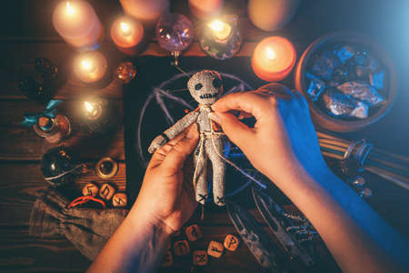 Sorceress or witch sticks needles into voodoo doll at ritual table with pentagram, burning candles and other occult objects, top view. Voodoo witchcraft, spirituality and occultism concept.