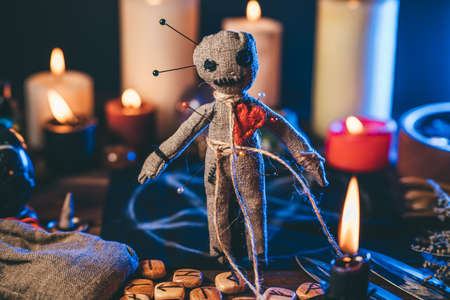 Voodoo doll studded with needles in magical table with candles and occult objects. Magic and dark spooky ritual. Retribution or revenge through witchcraft concept.
