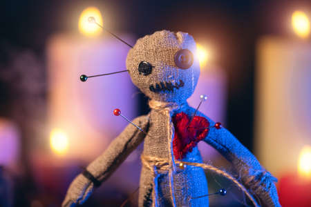 Voodoo doll studded with needles with pierced red rag heart against background of burning candles. Eerie or spooky magical esoteric ritual.