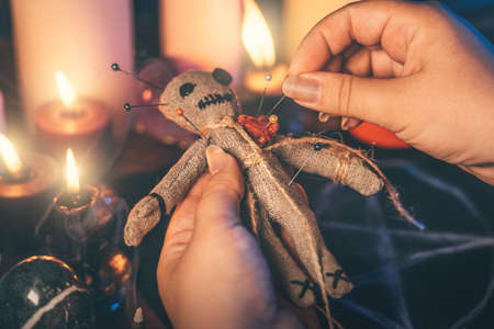 Female hands stick needles into body of rag voodoo doll. Witch performs sinister sorcery. Occult, esoteric and mystical rituals concept. Foto de archivo