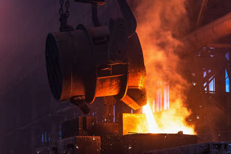 Molten metal is poured with sparks from ladle into mold. Smelting of multi-ton cast iron parts in foundry. Metallurgical plant or Steel Mill. Foto de archivo
