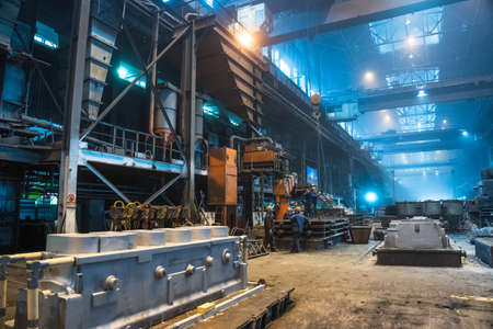 Interior of steel mill. Workers in workshop of metallurgical plant. Foundry and heavy industry building inside background.