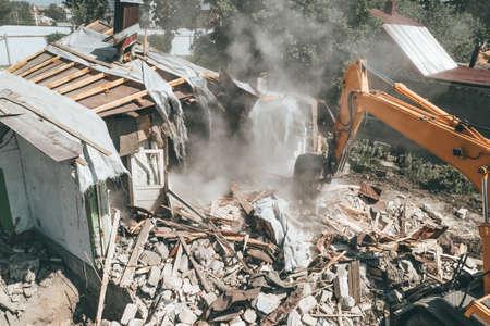 Destruction of old house by excavator. Bucket of excavator breaks concrete structure. Foto de archivo