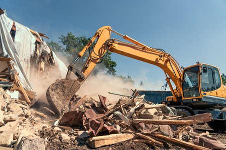 Destruction of old house by excavator with lot of dust. Bucket of excavator breaks concrete structure. Foto de archivo