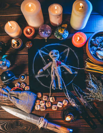 Voodoo doll on wooden table with candles and occult objects, top view. Magic and dark spooky ritual background, vertical poster image.