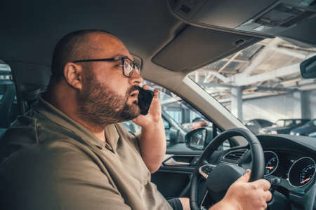 Fat man in glasses talking on cell phone while driving car in parking lot.