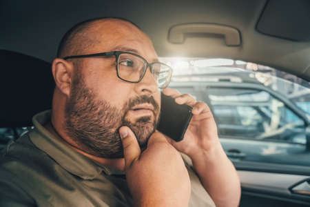 Puzzled man with glasses talking on phone while driving car. Emotion of doubt and distrust on face of funny fat man. Foto de archivo