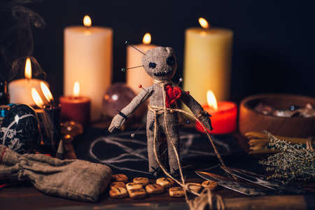 Voodoo doll on a magic table with esoteric objects and burning candles for a magical ritual of revenge.
