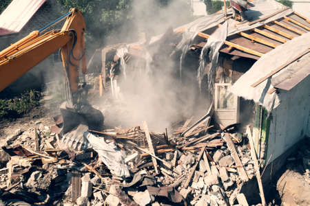 Process of demolition of old building dismantling aerial view. Excavator breaking house. Destruction of dilapidated housing for new development.